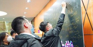 "Seniors were invited to sign their names on a class board at the auditorium entrance. At another station, seniors were encouraged to leave advice for freshmen, share favorite memories from their years at NYU Shanghai, and add to a ""Before I Graduate"" bucket list."